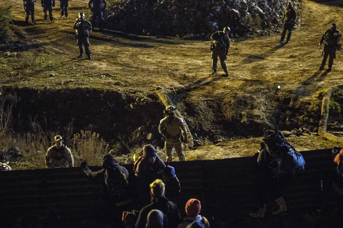 US border patrol officers deploy near the US-Mexico border fence to deter Central American migrants from crossing from Tijuana to San Diego, as seen from Tijuana, Baja California state, Mexico on January 1, 2019. - Around 100 Central American migrants made a failed attempt on New Year's Eve to cross over from Mexico into the United States. As night fell and people on both sides of the frontier prepared to celebrate New Year's Eve, the migrants tried to cross over but at least two smoke bombs were hurled and they ultimately held back.