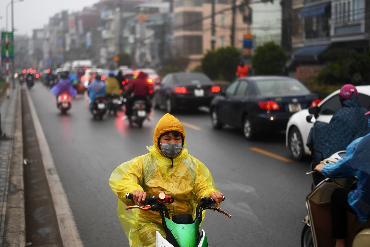 A young boy rides his electric scooter in the rain in Hanoi, Vietnam, on January 7th, 2019.