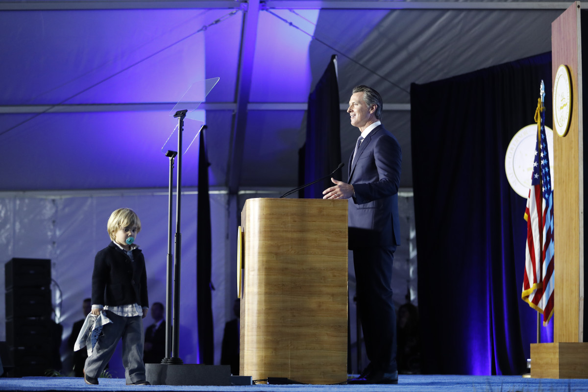 Governor Gavin Newsom delivers his inaugural address as his son Dutch, age two, walks on stage on January 7th, 2019, in Sacramento, California.