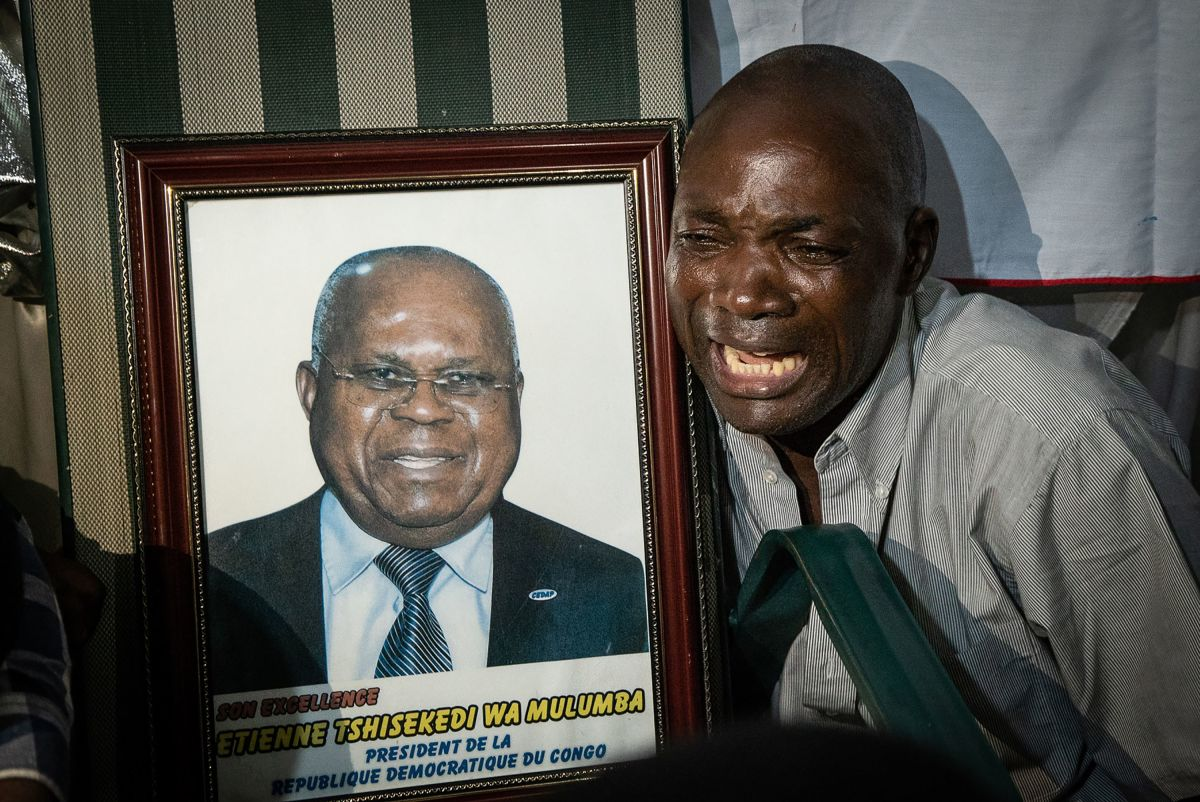 A supporter of Felix Tshisekedi reacts next to a picture of Etienne Tshisekedi, a Congolese political opponent who died in February of 2017 and father of the current candidate, after Felix Tshisekedi was named the provisional winner in the presidential election, at the former residence of Etienne Tshisekedi in Kinshasa on January 10th, 2019.