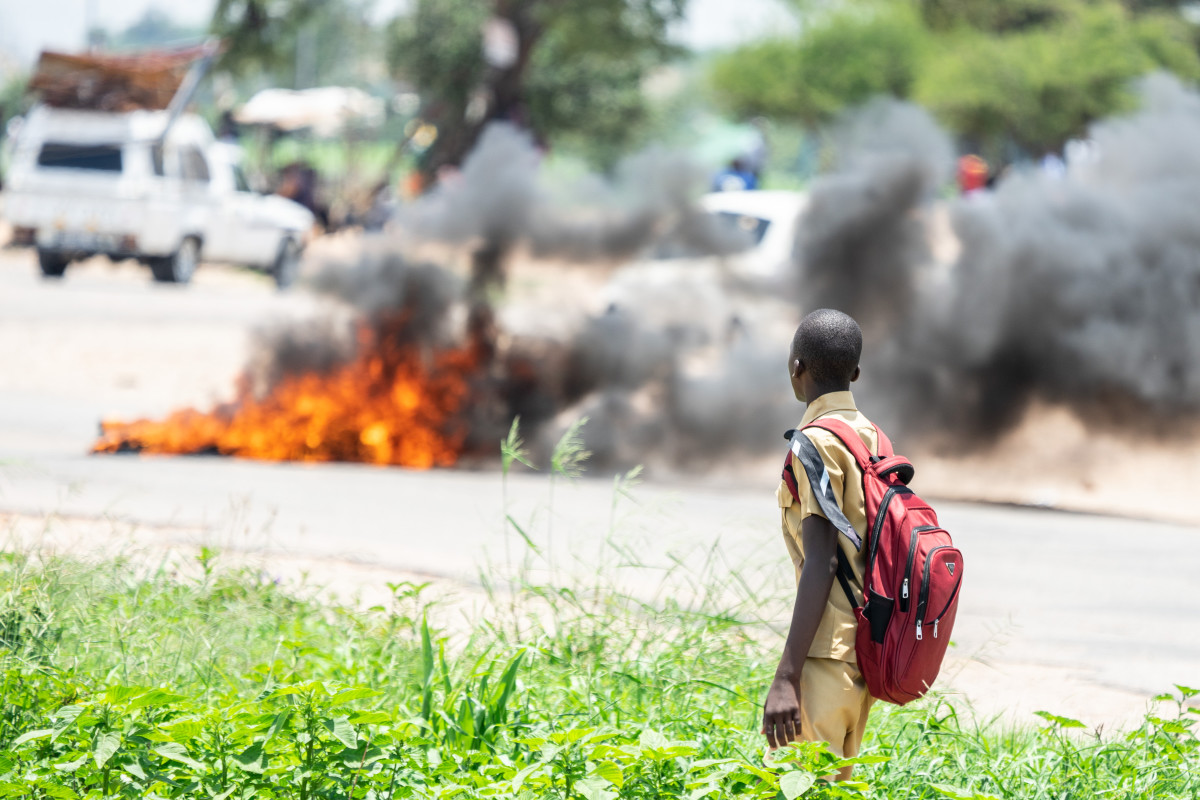 A school boy looks at a burning barricade during a demonstration on January 14th, 2019, in Bulawayo, Zimbabwe. Angry protesters barricaded roads with burning tires and rocks after the government more than doubled the price of fuel in a bid to improve supplies as the country battles its worst gasoline shortage in a decade.