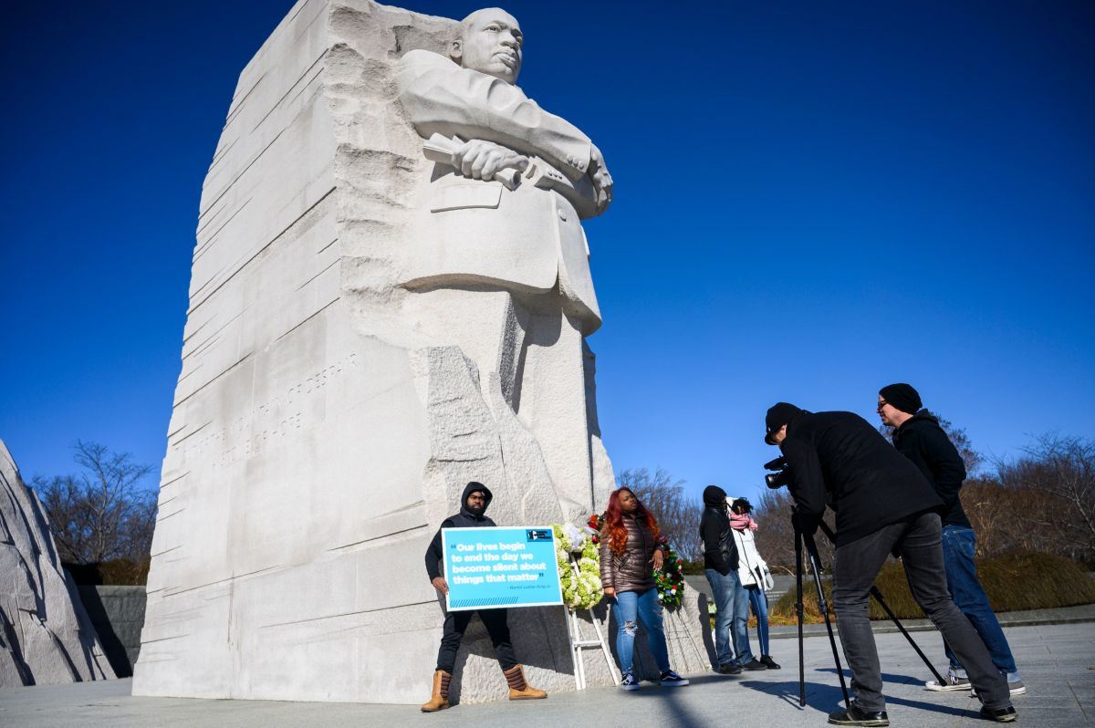 "People visit the Martin Luther King Jr. Memorial in Washington, D.C., for Martin Luther King Day on January 21st, 2019. The man holds a sign that quotes Martin Luther King Jr. It reads, ""Our lives begin to end the day we become silent about things that matter."""