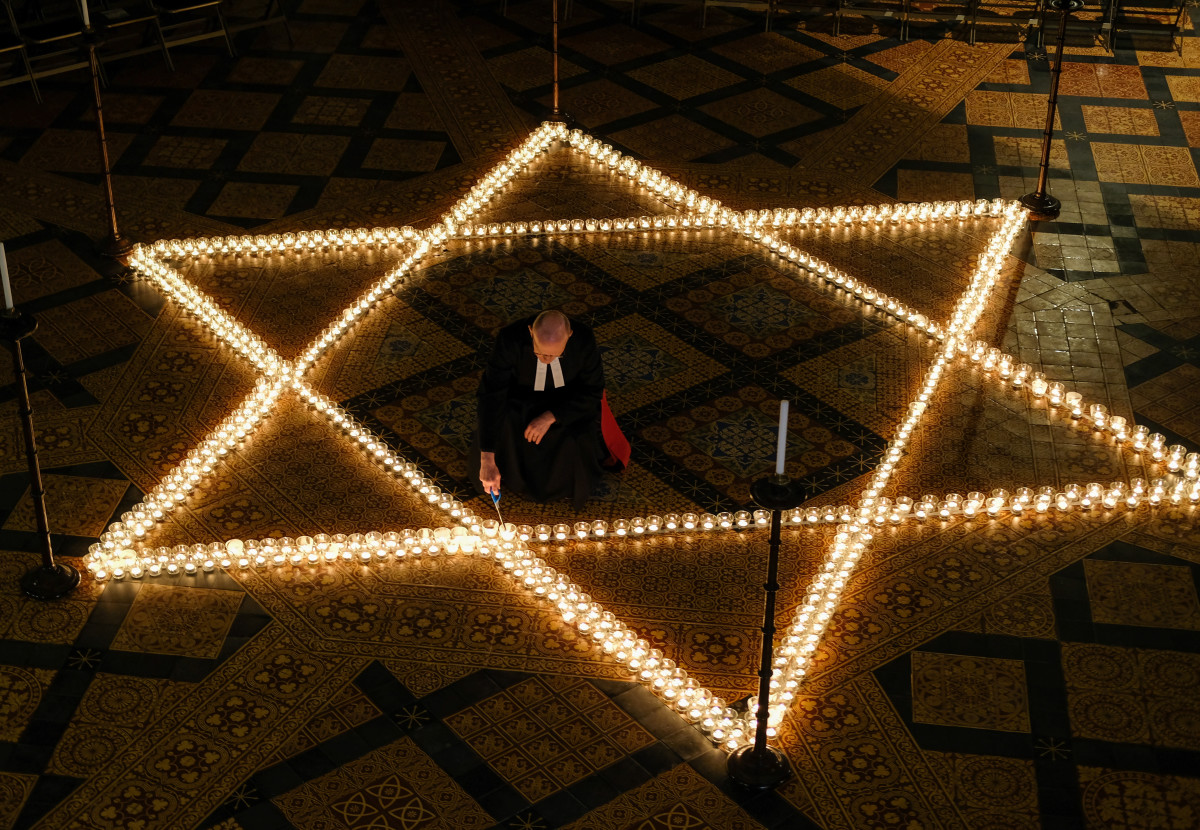 "The Reverend Canon Dr. Chris Collingwood, York Minster's Canon Chancellor, lights some of the 600 candles in the form of the Star of David set out on the floor during an event to commemorate Holocaust Memorial Day in the Chapter House at York Minster on January 24th, 2019, in York, England. The ceremony in the minster is one of many international events for Holocaust Memorial Day, held on January 27th. This date marks the liberation of the Auschwitz-Birkenau concentration camp in 1945. The international theme for Holocaust Memorial Day 2019 is ""Torn From Home,"" which encourages people to reflect on how the enforced loss of a safe place to call home is part of the trauma faced by anyone experiencing persecution and genocide. This year also marks the 25th anniversary of the Rwandan genocide, which began in April of 1994, and the 40th anniversary of the end of the Cambodian genocide, which ended in 1979."