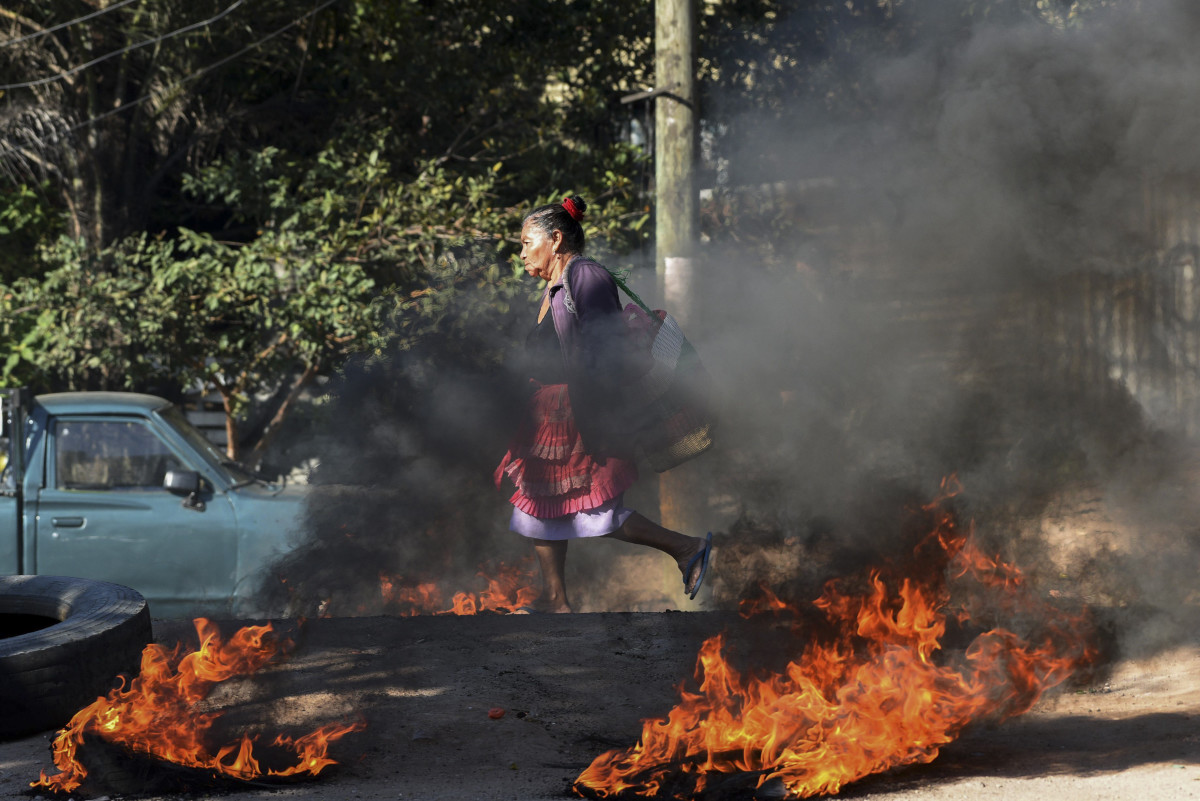 A woman walks through a roadblock mounted by supporters of the LIBRE opposition party in the El Carrizal neighborhood of Tegucigalpa, Honduras, on January 27th, 2019. The opposition is demanding that President Juan Orlando Hernández step down, a year after the start of his second term.