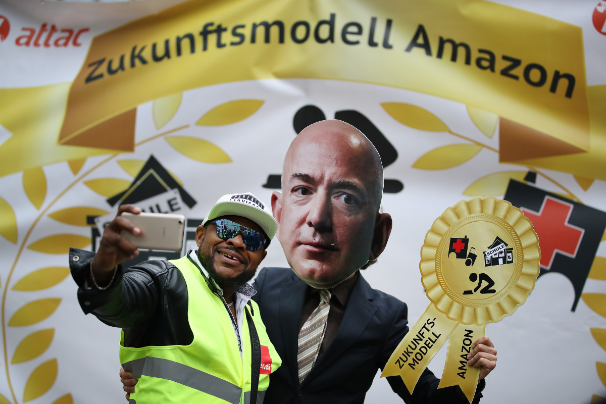 An Amazon warehouse worker shoots a selfie with an activist dressed as Amazon's Jeff Bezos during a protest outside the Axel Springer Building on April 24th, 2018, in Berlin.