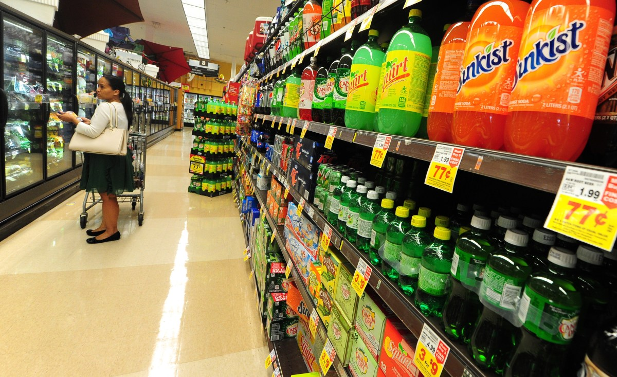A woman shops for frozen foods on an aisle across from sodas and other sugary drinks for sale at a supermarket in Monterey Park, California.