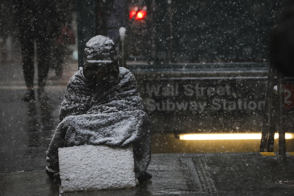 A homeless man sits in the falling snow in the Financial District on January 30th, 2019, in New York City.
