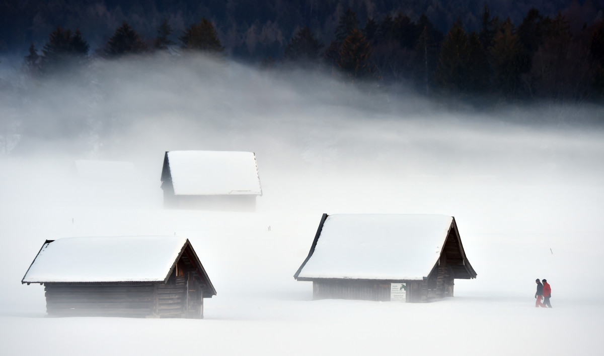 Pedestrian pass a snowy meadow way during foggy winter weather with temperatures by the freezing point in Garmisch-Partenkirchen, southern Germany, on January 27th, 2019.