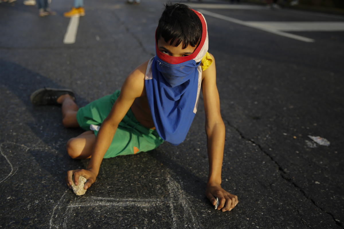 A young demonstrator writes slogans on the pavement during a protest against the government of President Nicolás Maduro in the streets of Caracas, Venezuela, on February 2nd, 2019.
