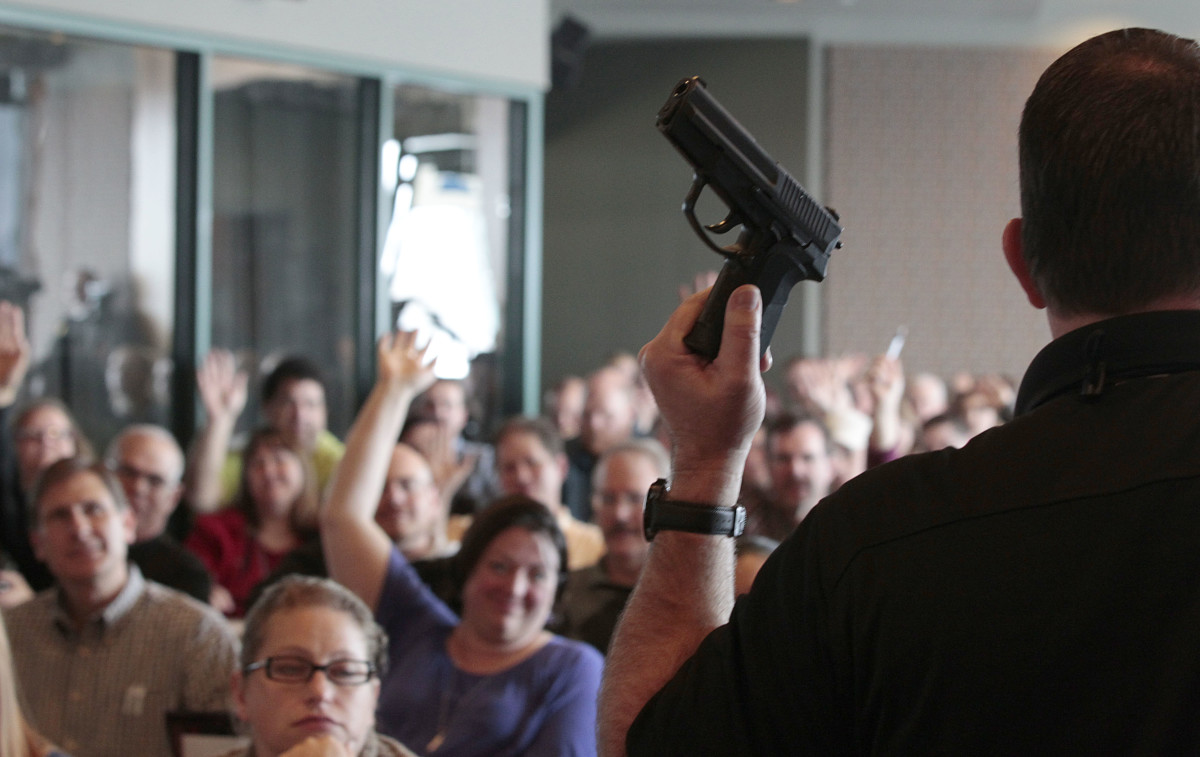 Firearm instructor Clark Aposhian holds a handgun up as he teaches a concealed-weapons training class to 200 Utah teachers in December of 2012. After the Marjory Stoneman Douglas High School shooting in Parkland, Florida, 14 state legislatures introduced bills calling to arm school staffs.
