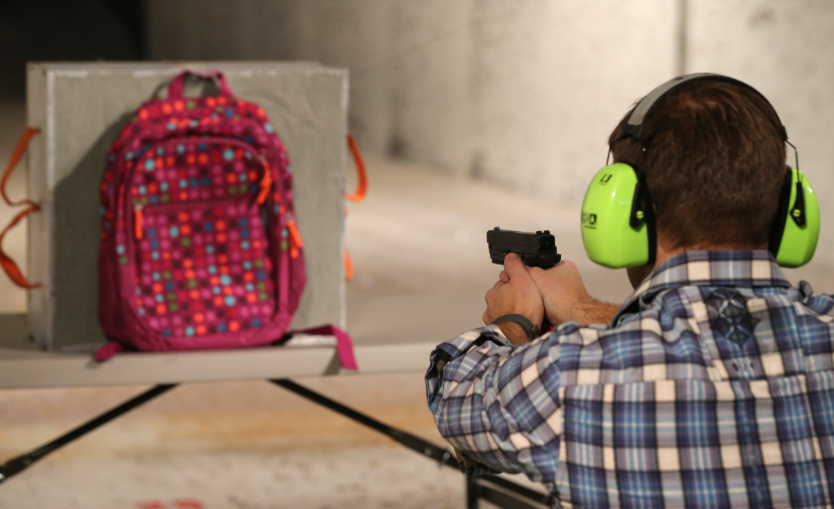 Chief operating officer for Amendment II, Rich Brand, shoots a child's backpack with the company's bulletproof shield inserted in it in December of 2012.