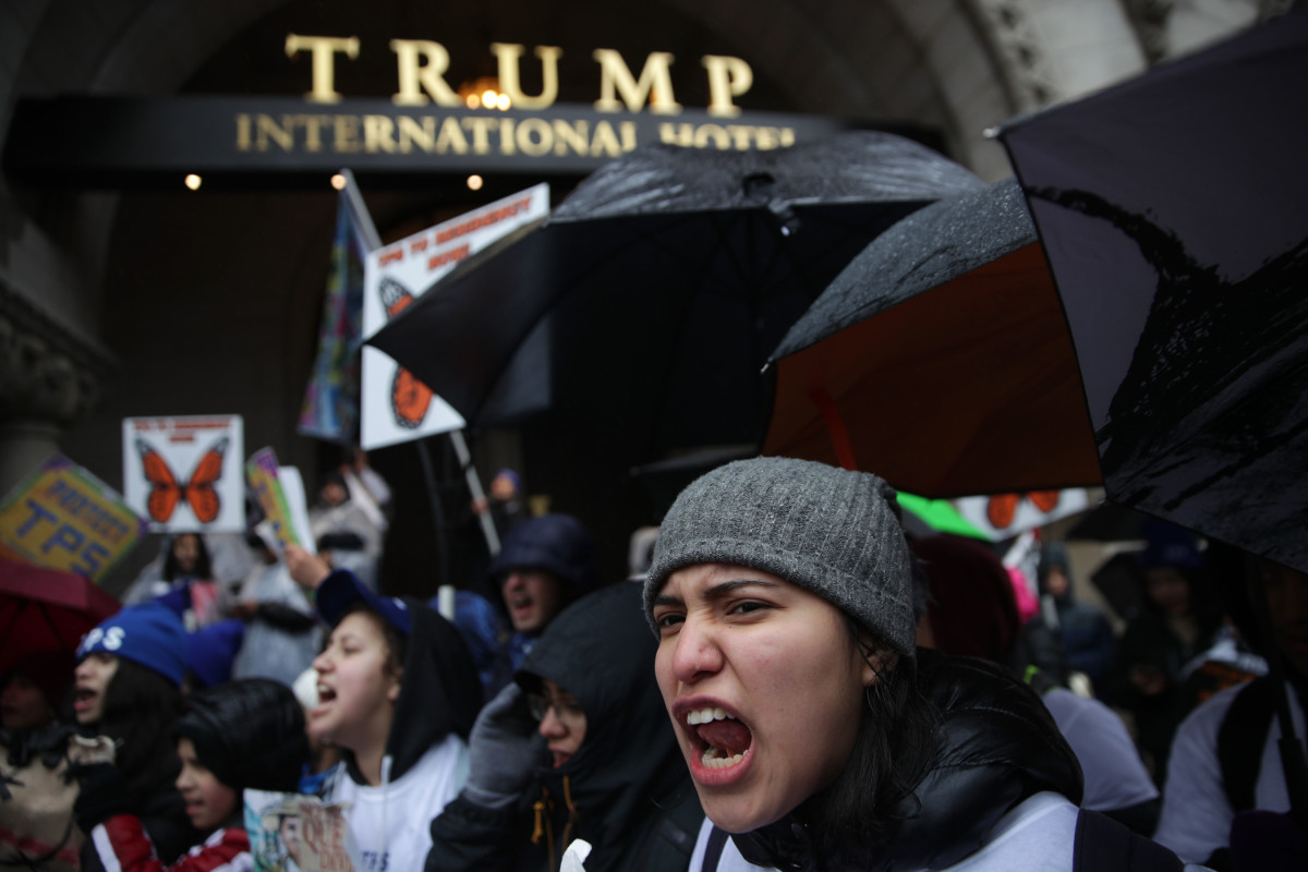 Immigration activists shout slogans as they protest outside Trump International Hotel during a march on February 12th, 2019, in Washington, D.C. Activists called on Congress to grant permanent protections to immigrants with Temporary Protected Status.