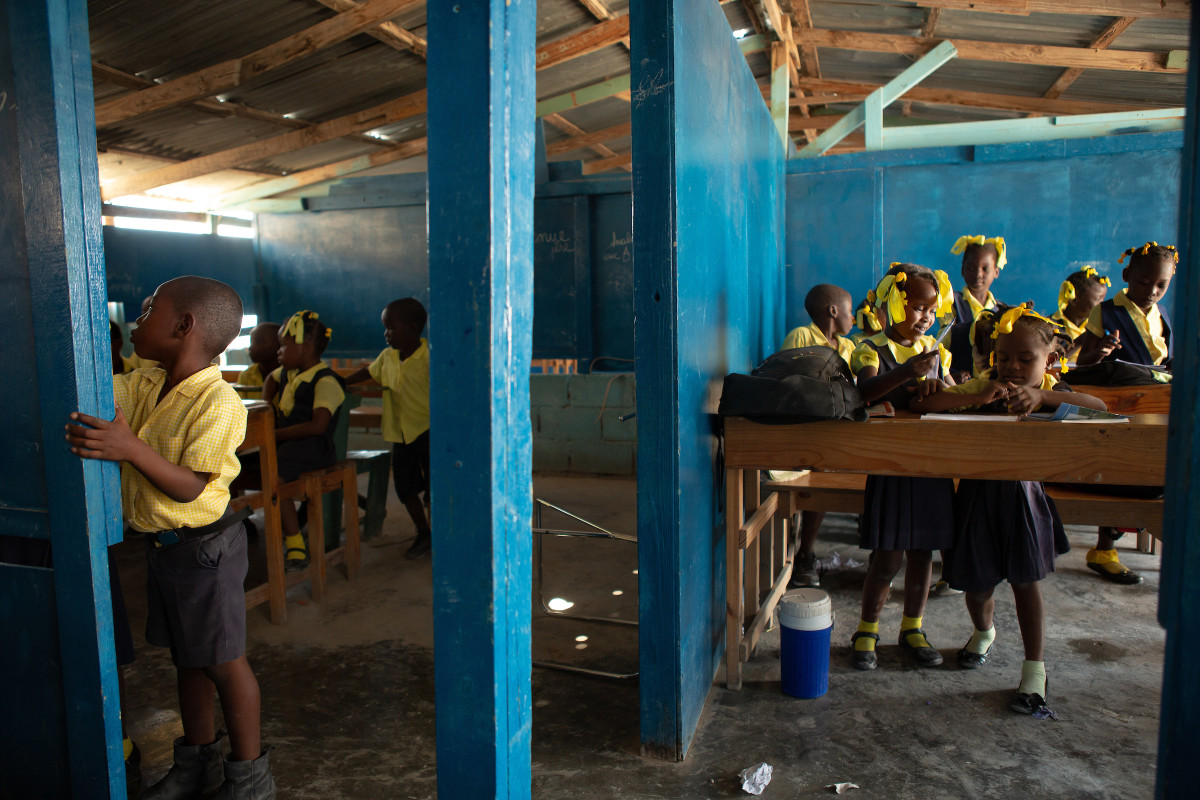 Students of various grades participate in classroom lessons in classrooms separated by partial walls at Institution Mixte Cean Carmen, a K-12 school in the Village de Pecheur neighborhood of greater Canaan.