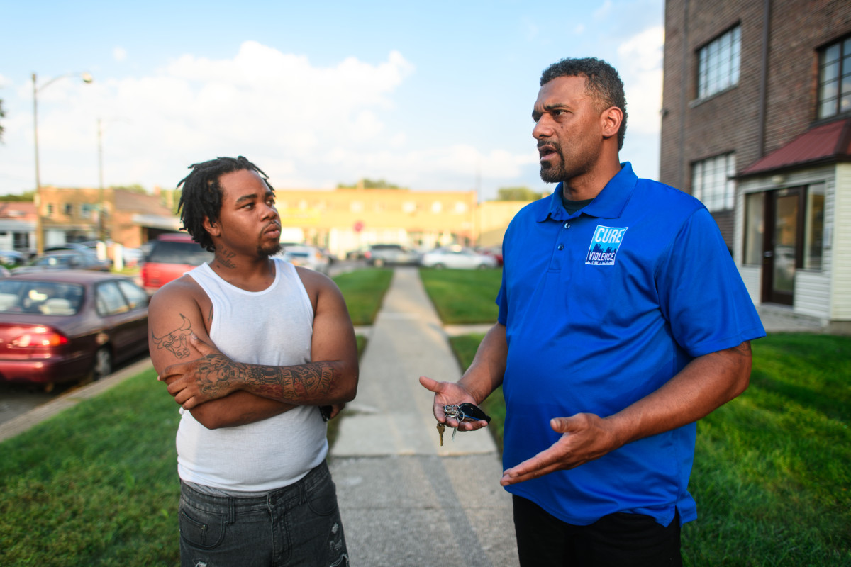 A Cure Violence outreach worker talks with a community member in Chicago.