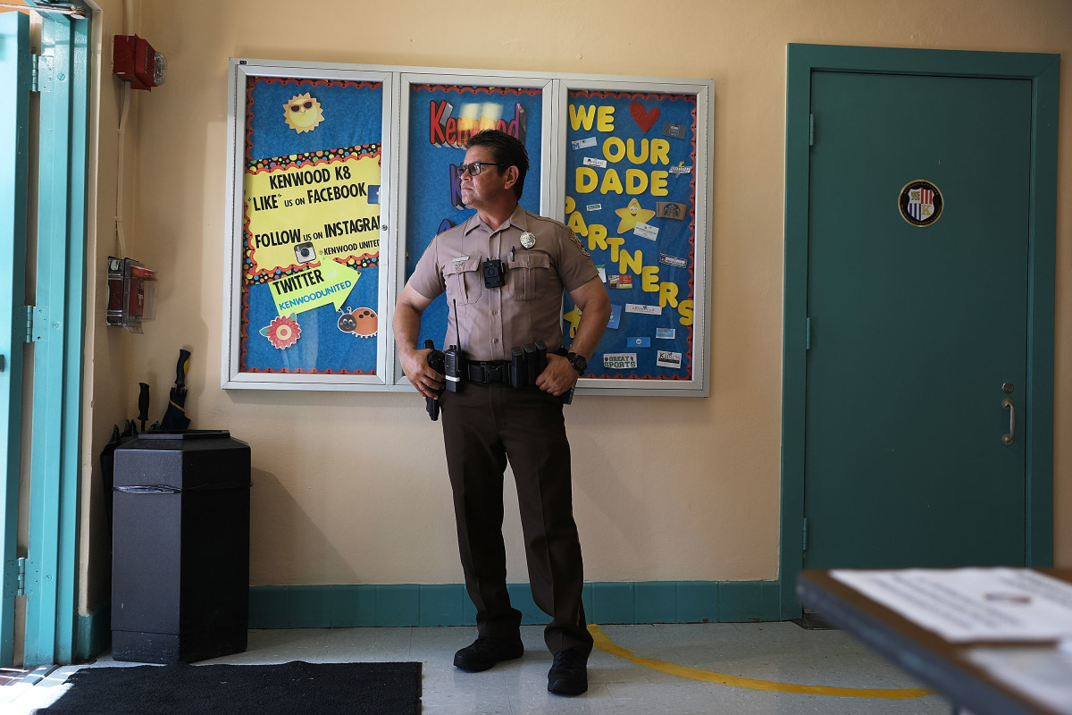 A Miami-Dade Police officer stands guard at the front entrance to the Kenwood K-8 Center in August of 2018 in Miami, Florida. In addition to armed police officers being present on school campuses, the school system has installed 15,000 high-definition cameras connected to a central command post as well as the Raptor system, which allows school personnel to check the criminal history of each school visitor.