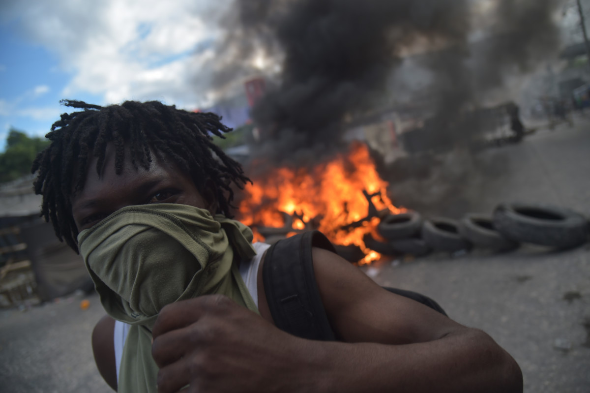 A demonstrator stands before a barricade of burning tires on the fourth day of protests in Port-au-Prince, Haiti, on February 10th, 2019. Demonstrators are demanding the resignation of Haitian President Jovenel Moise and protesting the misuse of nearly $2 billion from the PetroCaribe fund.