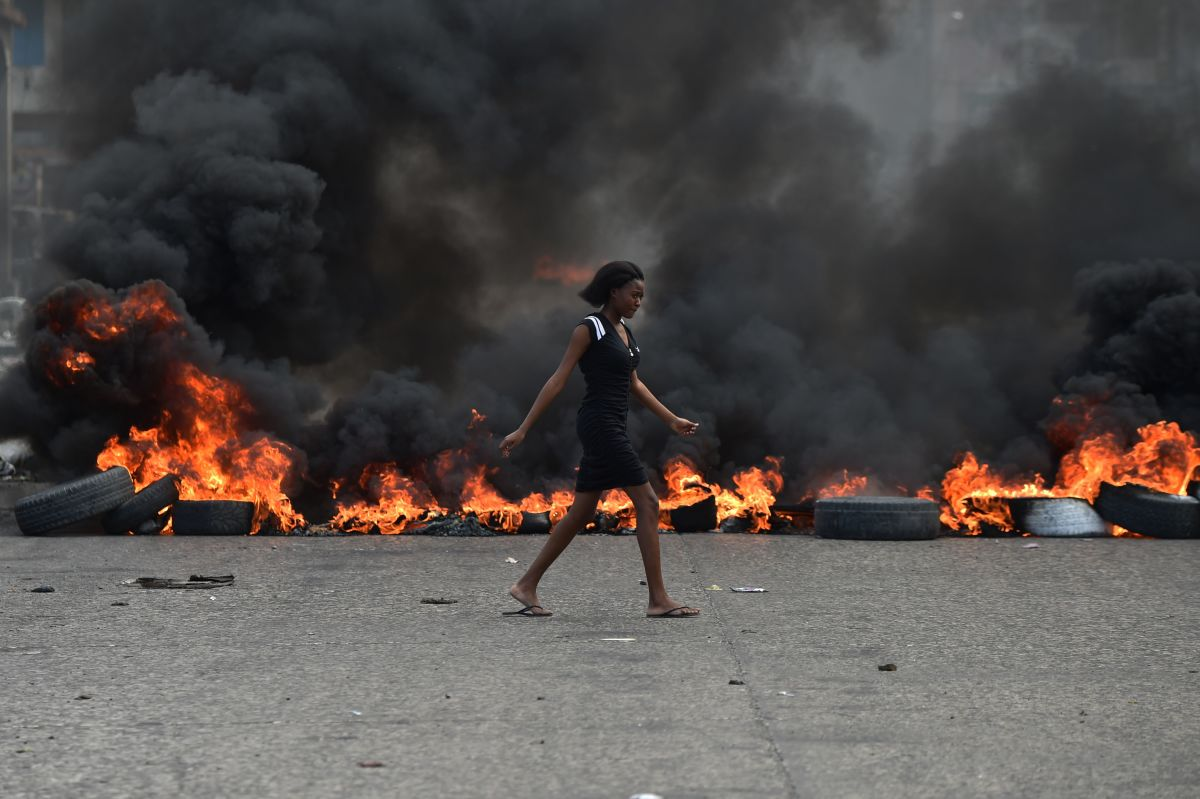 A woman walks past tire barricades set ablaze by demonstrators on February 10th, 2019, the fourth day of protests in Port-au-Prince.