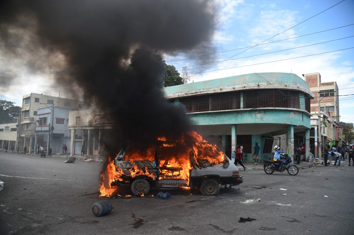 A burning car is seen during clashes in the center of Haitian capital Port-au-Prince on February 12th, 2019, during the sixth day of protests against Haitian President Jovenel Moise and misuse of the PetroCaribe fund.