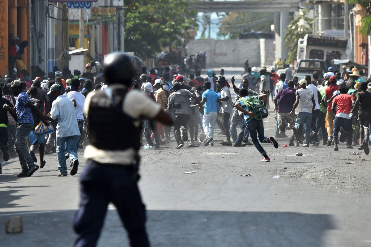 Demonstrators flee as Haitian police open fire during the clashes in the center of Port-au-Prince on February 13th, 2019, the seventh day of protests against Haitian President Jovenel Moise and the misuse of the PetroCaribe fund.