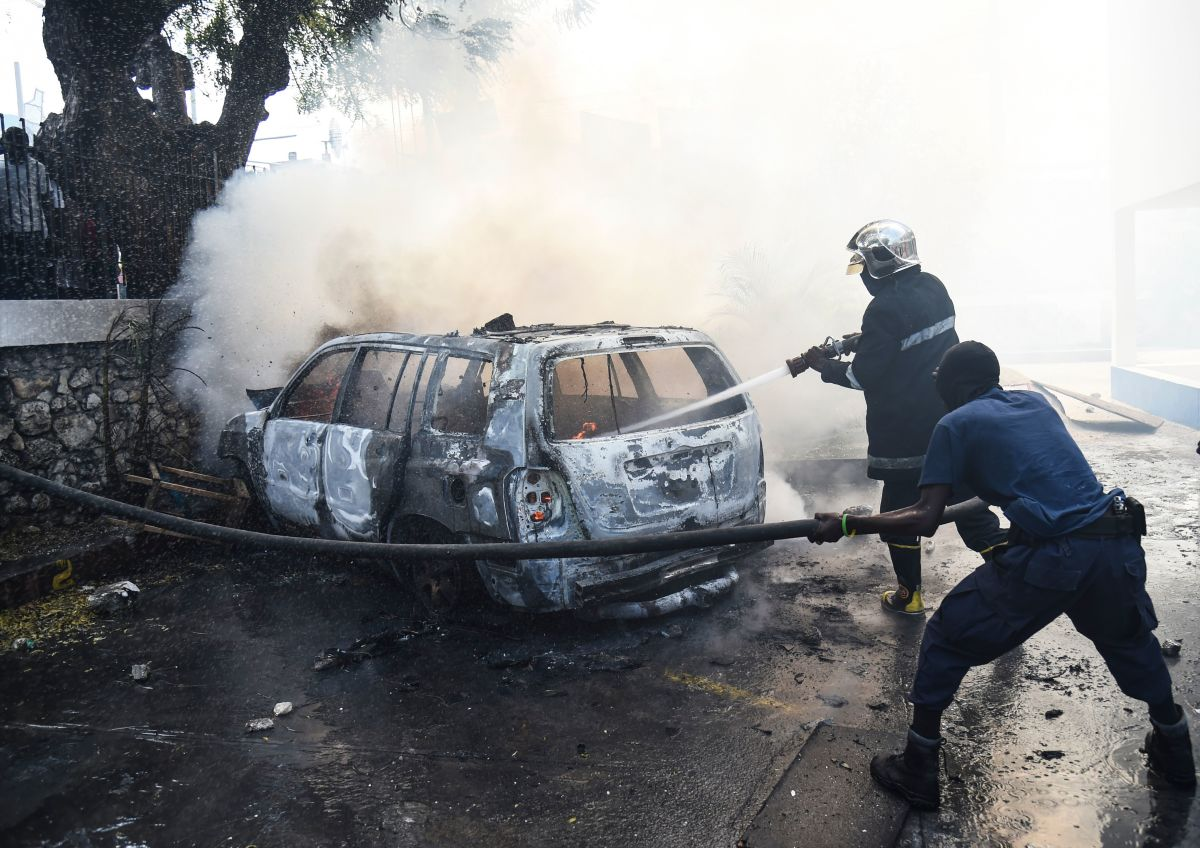 Firemen extinguish burning cars at the offices of Television Nationale d'Haiti in the Haitian capital of Port-au-Prince, on February 13th, 2019, the seventh day of protests against Haitian President Jovenel Moise and the misuse of the PetroCaribe fund.