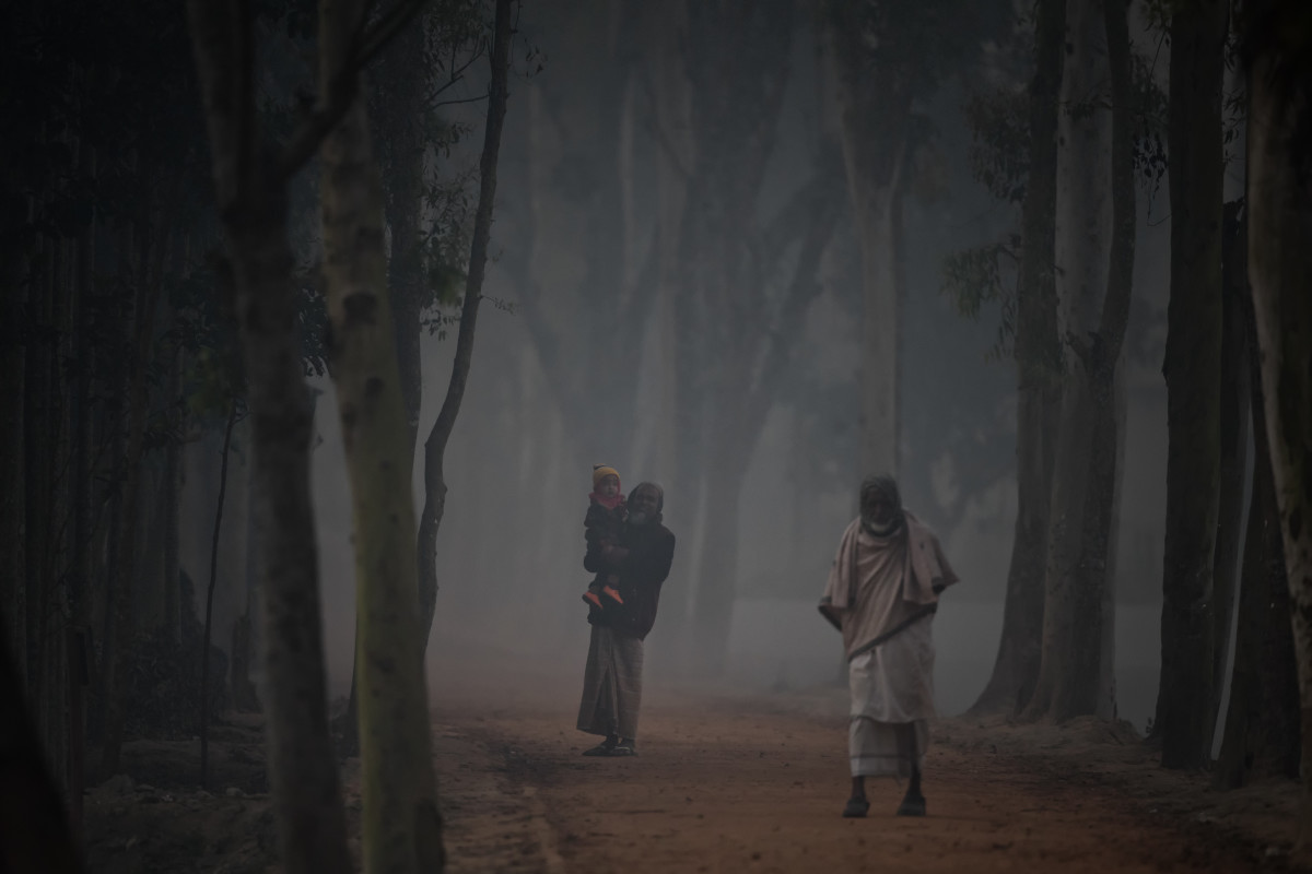 Two men walk along a road that is otherwise still under a blanket of wood smoke and dawn mist.