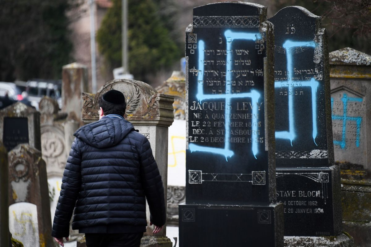 A man walks by graves vandalized with swastikas at the Jewish cemetery in Quatzenheim, France, on February 19th, 2019, the day of a nationwide march against a rise in anti-Semitic attacks. Around 80 graves have been vandalized at the Jewish cemetery in the village, close to the border with Germany in the Alsace region. The graffiti was discovered early Tuesday, according to a statement from the regional security office.