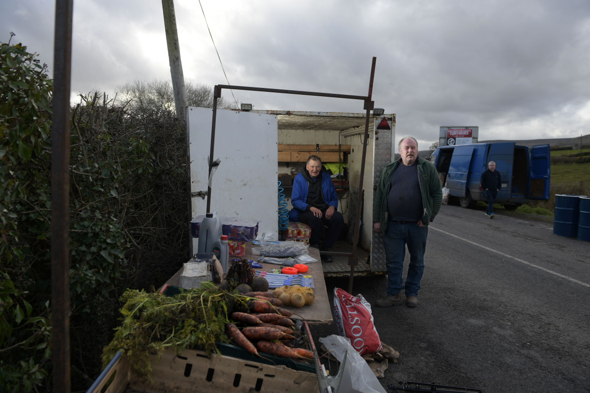 Denny Johnston (right) poses for a photograph alongside John Taylor (left) as he trades from the back of his trailer on the Irish border at the Mullan roadside market on February 17th, 2019, in Mullan, Northern Ireland. Johnston, who buys and sells his goods on both sides of the border, fears for his business if a hard border returns.