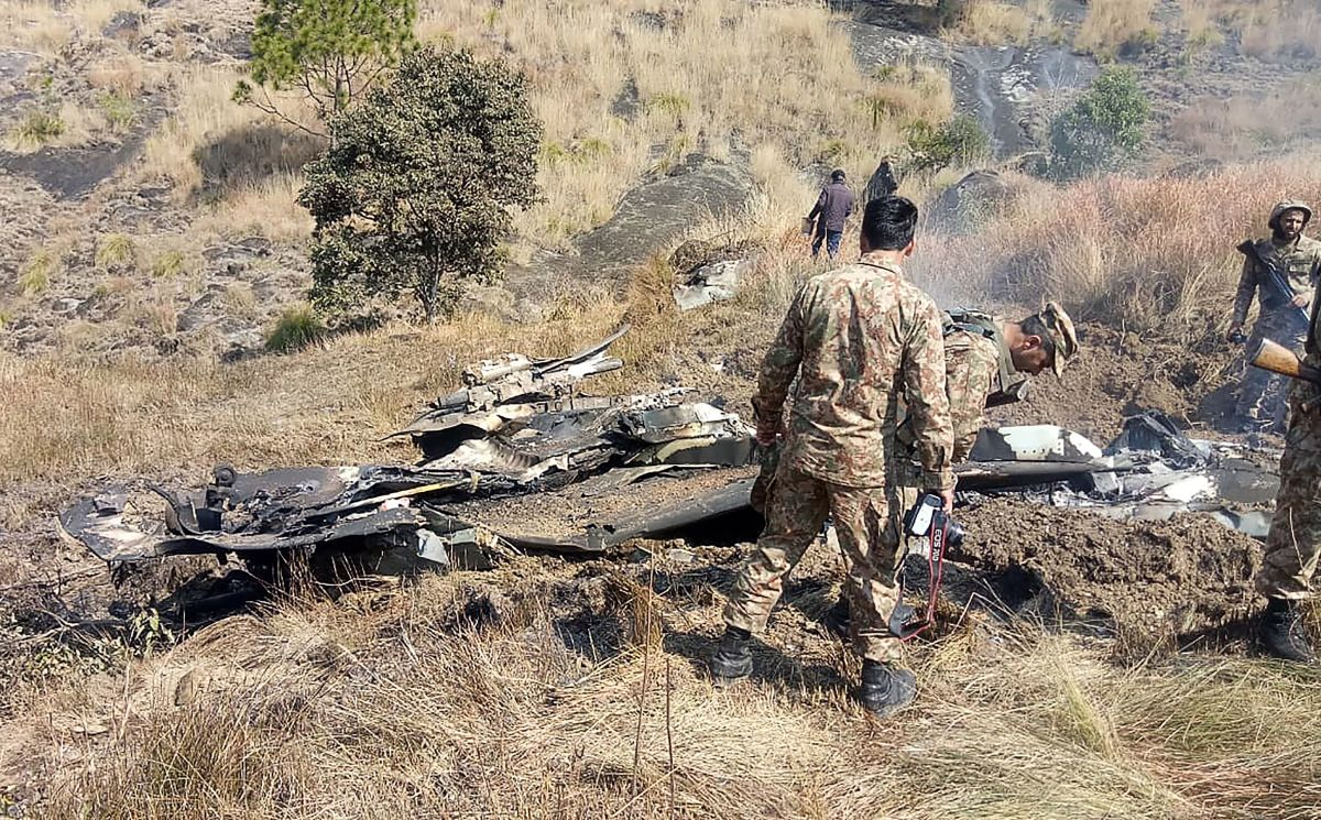 Pakistani soldiers stand next to what Pakistan says is the wreckage of an Indian fighter jet shot down in Pakistan-controlled Kashmiron on February 27th, 2019.