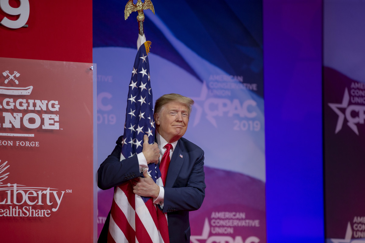 President Donald Trump hugs the United States flag during CPAC 2019 on March 2nd, 2019.