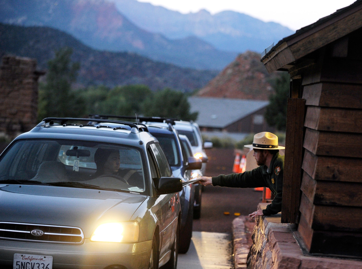A park ranger Lee Wilson (R) passes out park information to visitors at the entrance to Zion National Park in Springdale, Utah.