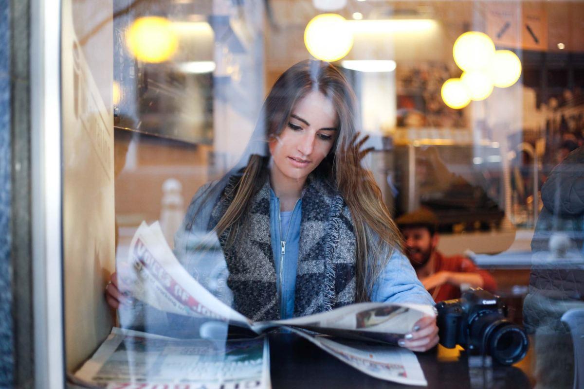 Woman reading newspaper news media