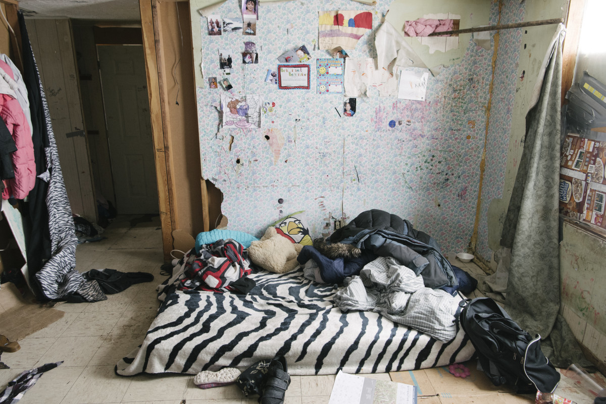 A single mattress covers the floor of a three-person household. Mattresses and furniture in general are scarce on Saint Lawrence Island, and nearly all structures appear to consist solely of exterior shells built by the U.S. government decades ago.