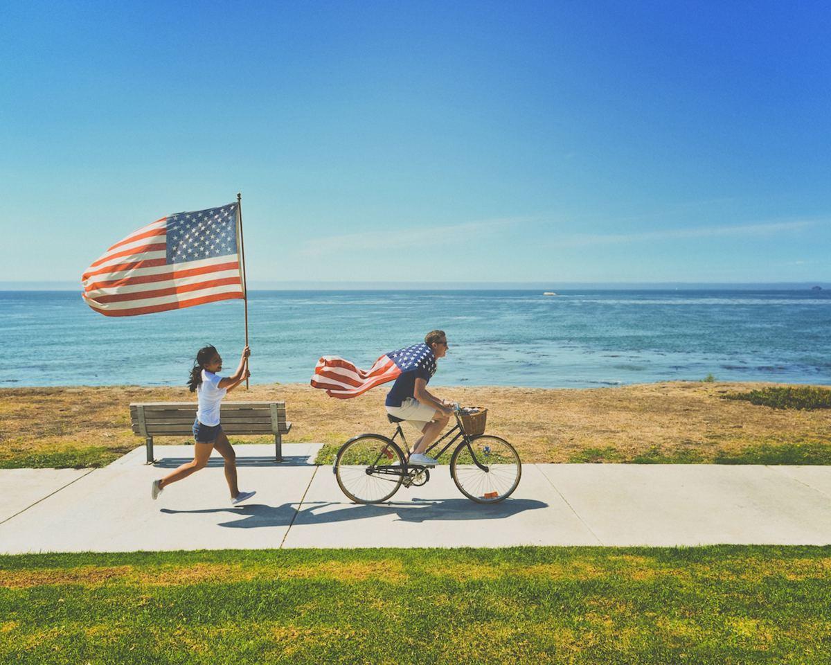 man woman american flag beach water ocean