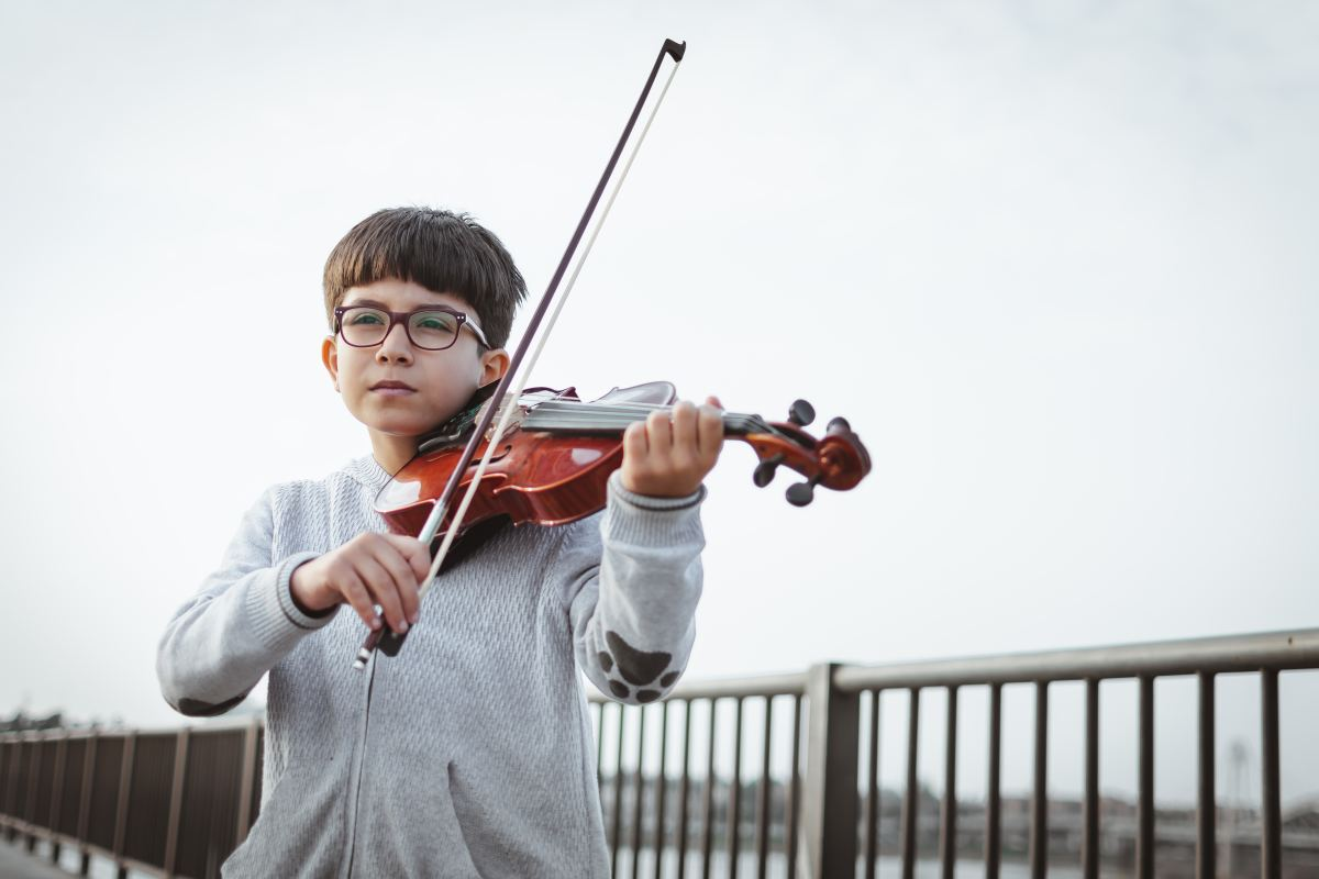Boy playing violin child music education