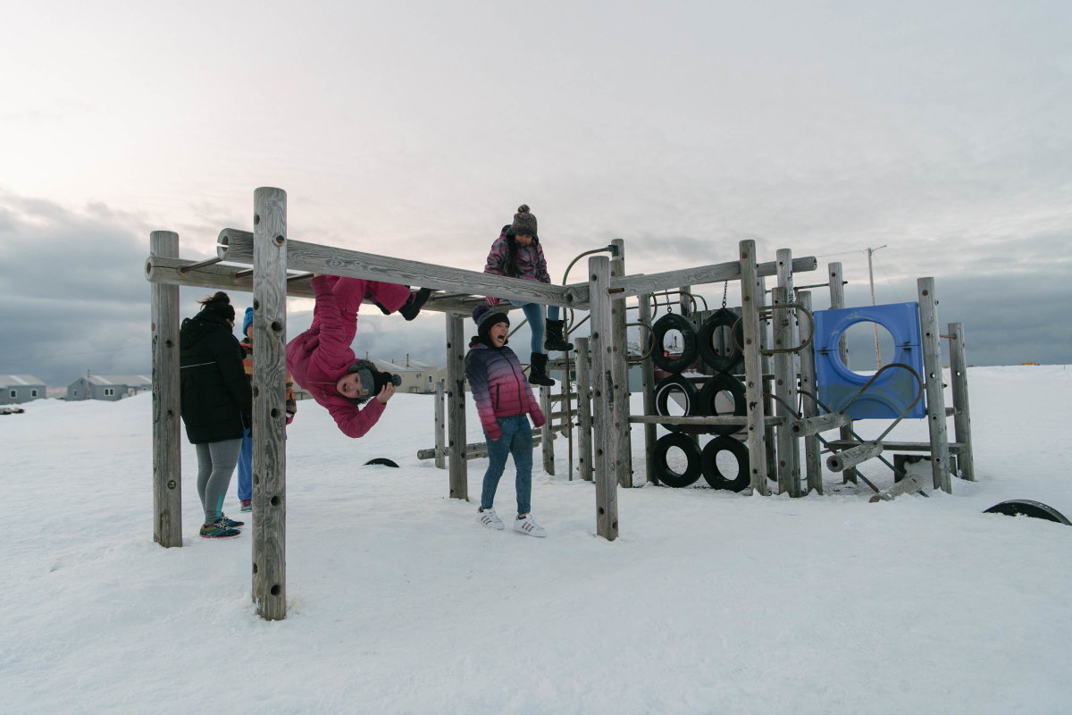 Kids play on a snowy playground in the light of Arctic spring. With each new generation, the traumas experienced by previous generations grow more distant, though the community's youth will undoubtedly face new challenges as they come of age.