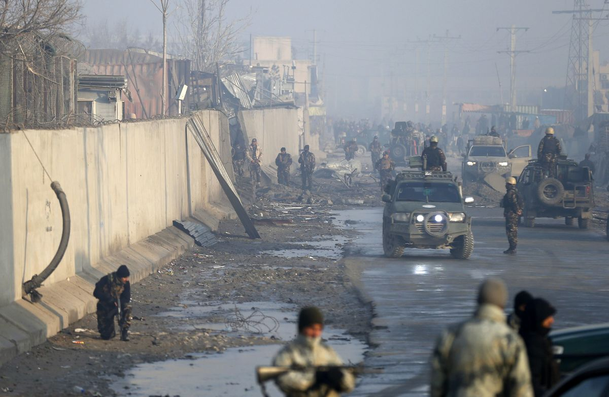 Afghan security forces gather in mid-January at the site of a powerful truck bomb attack, claimed by the Taliban, which killed four and wounded over 100.