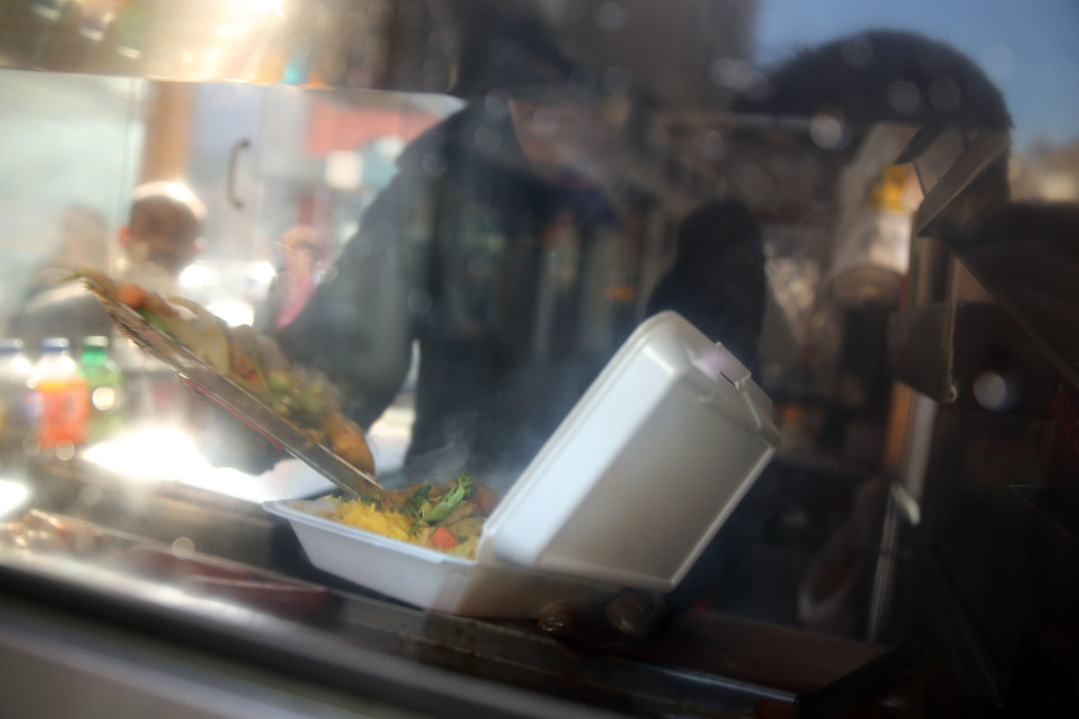 A food cart worker fills a styrofoam take-out container with food for a customer on December 19th, 2013, in New York City.