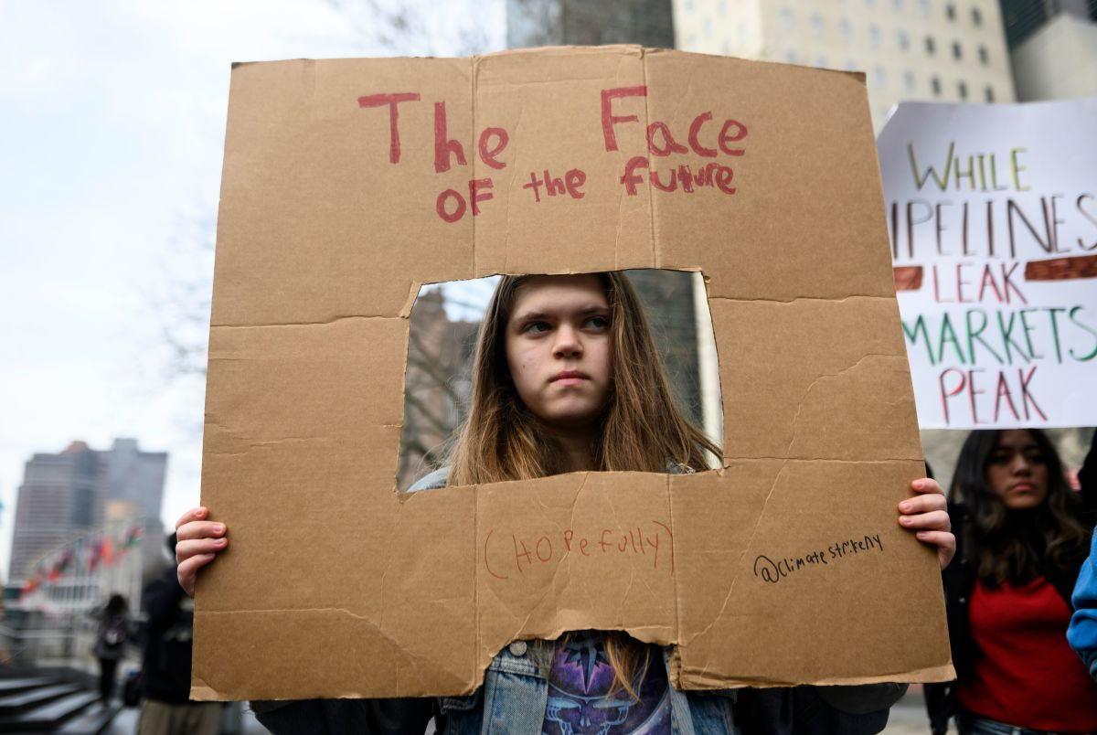 "A girl holds a sign reading, ""The Face of the Future (Hopefully),"" during a Youth Climate Strike in front of the New York headquarters of the United Nations on March 15th, 2019."