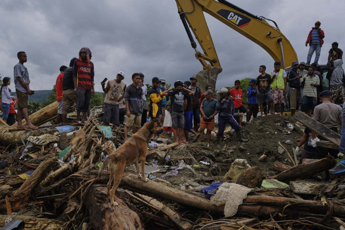 Indonesians watch as rescue workers dig through rubble looking for victims of the recent flash floods on March 19th, 2019, in Sentani, West Papua province, Indonesia. At least 89 people have died and nearly 7,000 have been displaced from their homes after three straight days of heavy rain led to massive flash flooding, which brought down massive trees and boulders from the surrounding mountains, crushing hundreds of homes.