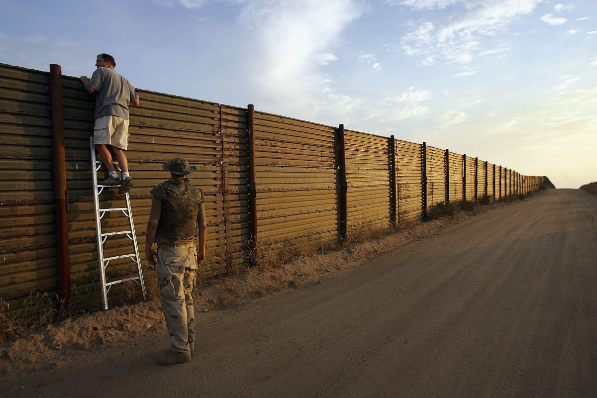 Volunteers look over the U.S.–Mexico border fence.