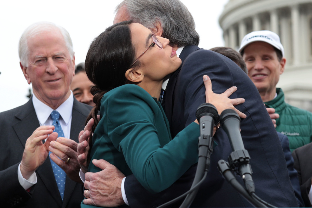 Representative Alexandria Ocasio-Cortez and Senator Ed Markey hug each other as other Congressional Democrats look on during a news conference unveiling a Green New Deal resolution in front of the U.S. Capitol on February 7th, 2019, in Washington, D.C.