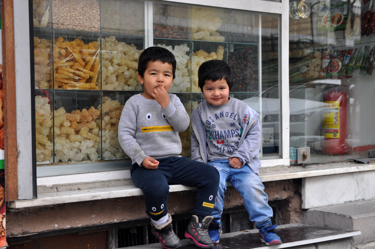 Emmar, 4, and Muhammed, 3, sit outside a candy shop near their father's cell phone store. The neighborhood of Zeytinburnu boasts one of Istanbul's largest collections of Uyghur-owned shops, businesses, and restaurants.