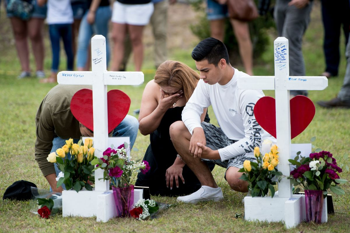 People visit a cross for Christopher Stone at a memorial for the victims of the Santa Fe High School shooting on May 21st, 2018, in Santa Fe, Texas.