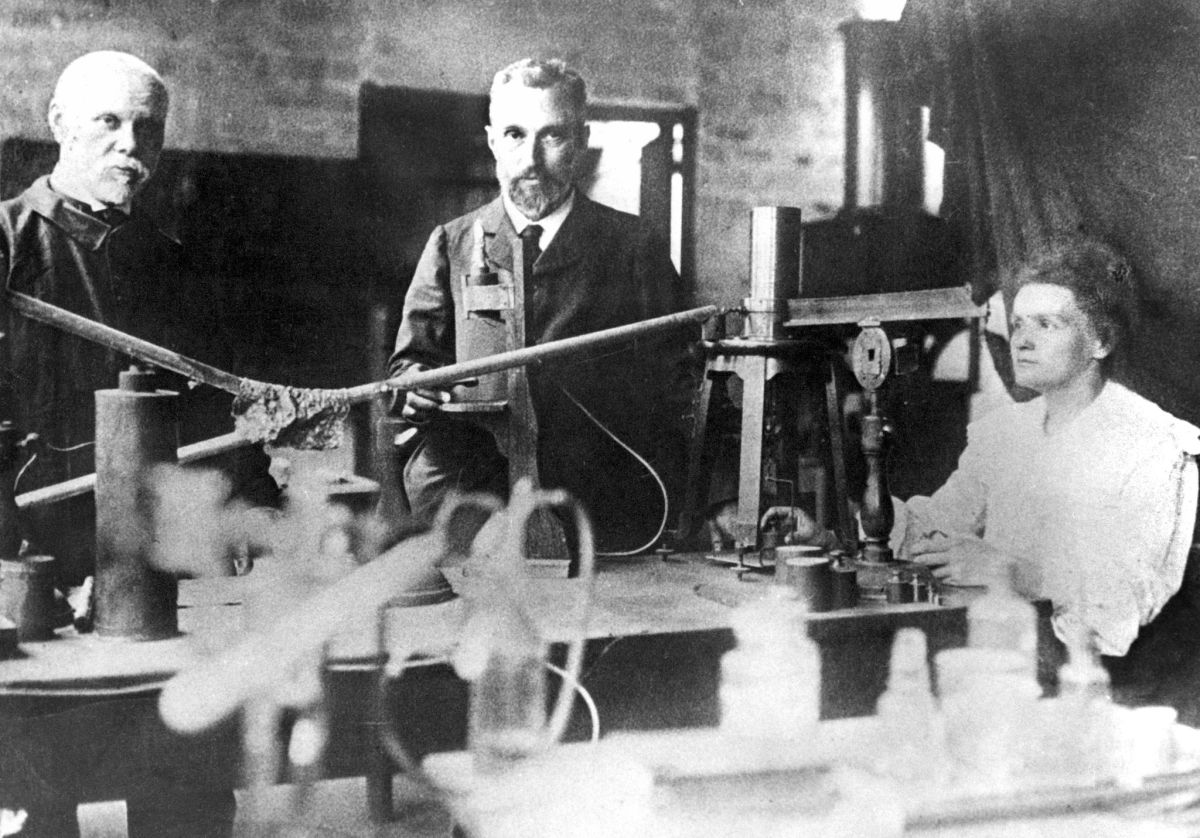 This picture from around 1900 shows Marie Curie (right), her husband Pierre (center), and assistant Edison Petit (left) working in their makeshift laboratory in Paris. Marie Curie and her husband discovered radium and won the Nobel prize for physics in 1903. Marie Curie was the first person to receive two Nobel prizes when she was awarded the Nobel prize for chemistry in 1911.