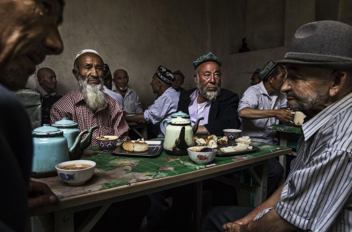 Uyghur men talk at a teahouse in the old town of Kashgar in Xinjiang province, China, on July 1st, 2017. Kashgar has long been considered the cultural heart of Xinjiang for the province's nearly 10 million Muslim Uyghurs.