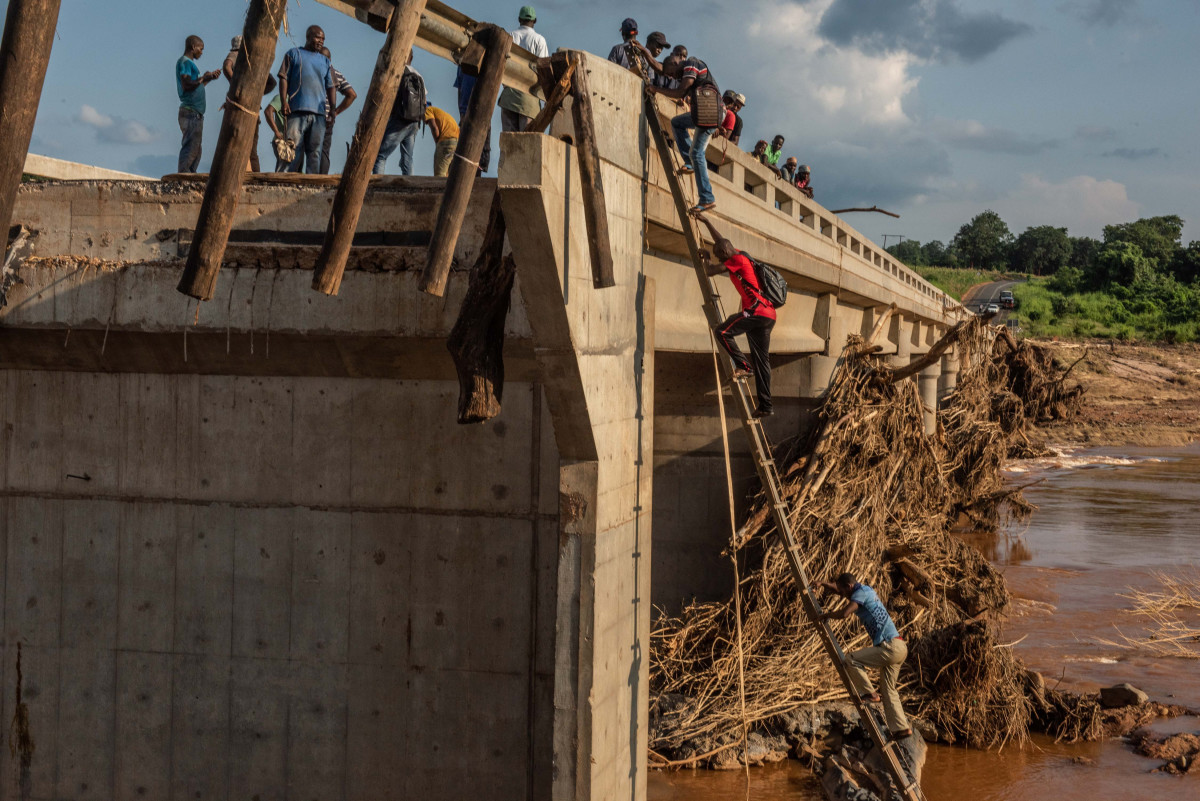 People scale a broken bridge, damaged during Cyclone Idai, to cross the Lucite River on March 26th, 2019, outside of Magaro, Mozambique. The storm caused the river to overflow and flood nearby villages. At least 156 bodies have been found in the surrounding area.
