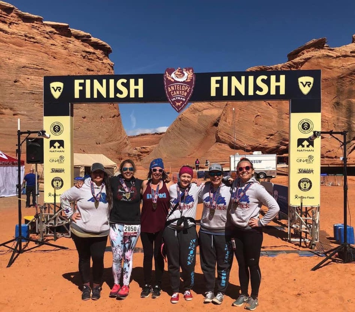 Members of the Kwe Pack celebrating recently at the finish line of the Antelope Canyon Half-Marathon. Left to right: Chally Topping, Sharon Avery, Jen Trotterchaude, Melissa Walls, Alicia Kozlowski Cyr, and Sarah Agaton Howes.