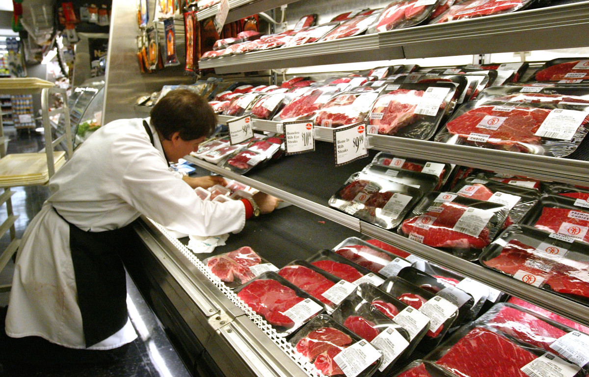 A butcher arranges meat products at a grocery December 29th, 2003, in New York City.