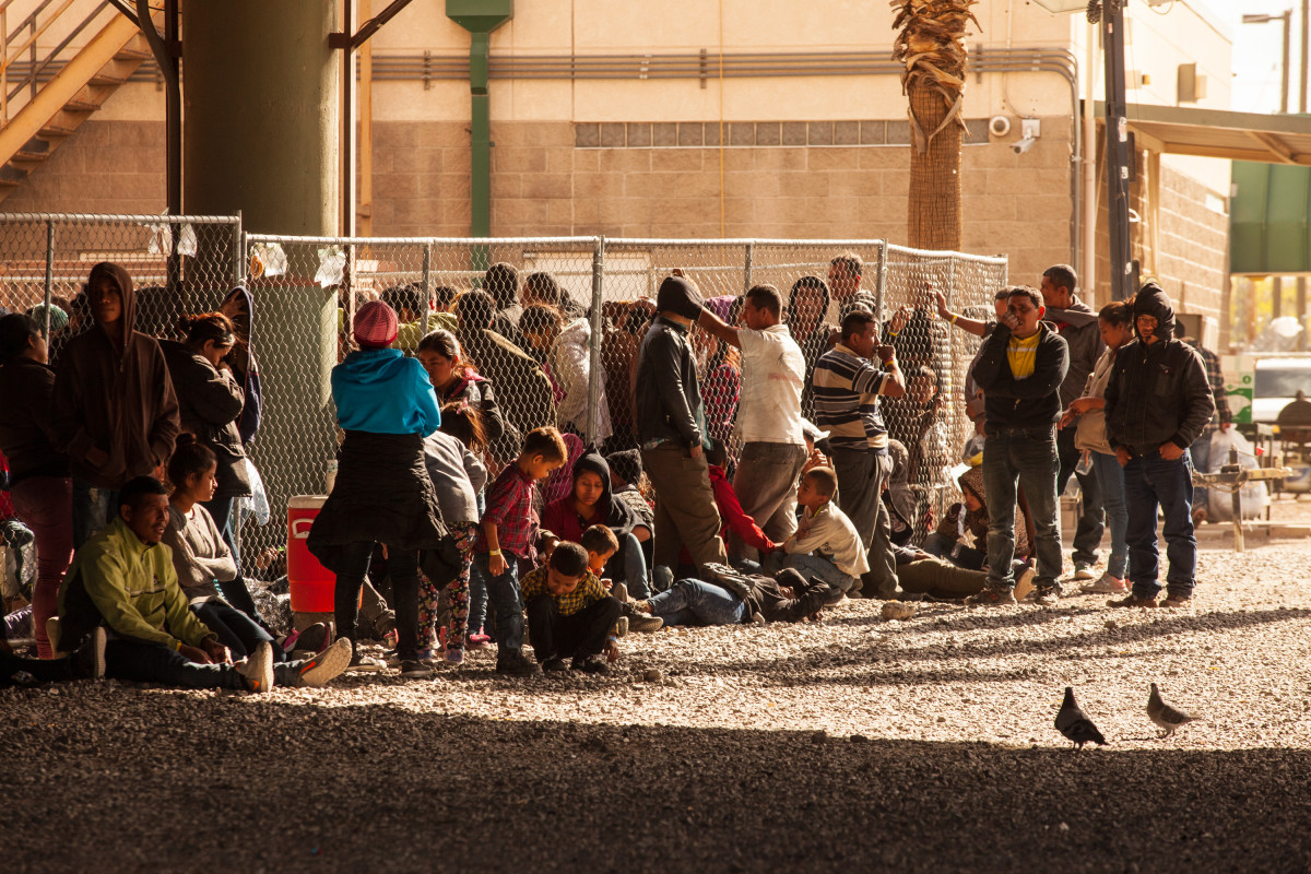 Migrants and asylum seekers awaiting processing are held in temporary fencing underneath the Paso Del Norte Bridge on March 28th, in El Paso, Texas. U.S. Customs and Border Protection has temporarily closed all highway checkpoints along the 268-mile stretch of border in the El Paso sector.