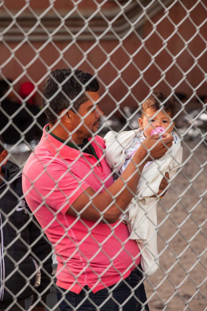 A man holds a child as both wait along with hundreds of other people in the temporary enclosure on March 28th.